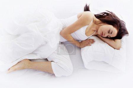 Photo pour Stock image de jeune femme allongée sur le lit blanc - image libre de droit