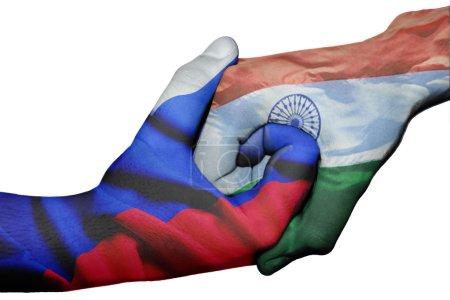 Photo pour Poignée de main diplomatique entre pays : drapeaux de la Russie et l'Inde surimprimé les deux mains - image libre de droit