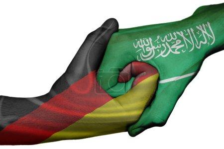 Photo pour Poignée de main diplomatique entre pays : drapeaux de l'Allemagne et l'Arabie saoudite a surimprimé les deux mains - image libre de droit