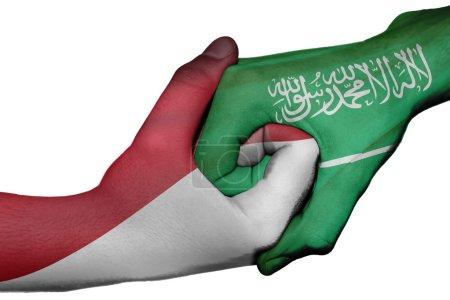 Photo pour Poignée de main diplomatique entre pays : drapeaux de l'Indonésie et l'Arabie saoudite a surimprimé les deux mains - image libre de droit