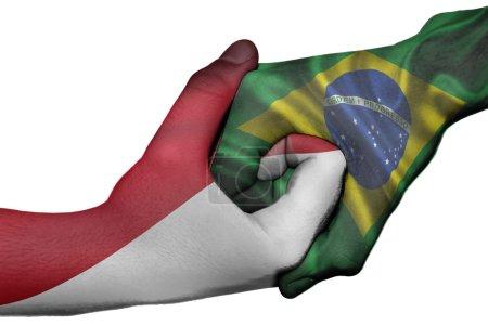 Photo pour Poignée de main diplomatique entre pays : drapeaux de l'Indonésie et le Brésil a surimprimé les deux mains - image libre de droit