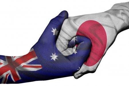 Photo pour Poignée de main diplomatique entre pays : drapeaux de l'Australie et le Japon surimprimé les deux mains - image libre de droit
