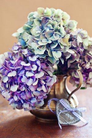 Foto de Flores de hortensias púrpura y un corazón de madera sobre una mesa. - Imagen libre de derechos