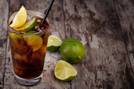 Photo for Cuba Libre Drink with lime on a wooden table - Royalty Free Image