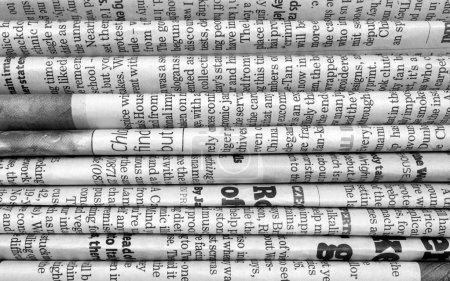 Photo for A black and white background of English language newspapers stacked and folded in a horizontal position and viewed in close up - Royalty Free Image