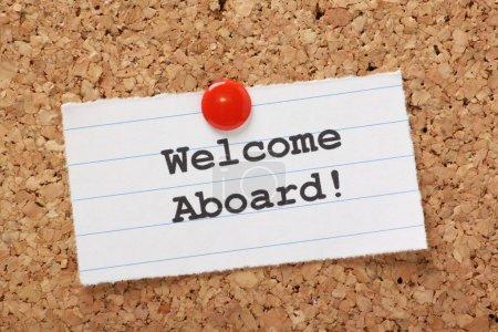 Photo pour L'expression Bienvenue à bord ! tapé sur un morceau de papier ligné et épinglé à un panneau d'affichage Liège. une expression utilisée pour accueillir un nouveau membre de l'employé ou équipe. - image libre de droit