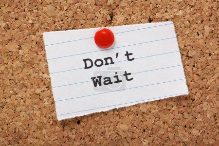 Photo pour N'attendez pas tapé sur un morceau de papier ligné et épinglé à un panneau d'affichage Liège. un appel à agir et faire avancer les choses plutôt que de perdre du temps et la procrastination. - image libre de droit