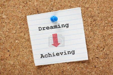 Photo pour Une flèche pointant le chemin de Rêver à Réaliser sur une note en papier épinglée sur une planche de liège. Nous avons tous des rêves, des plans et des objectifs, mais nous devons prendre des mesures pour les concrétiser. . - image libre de droit
