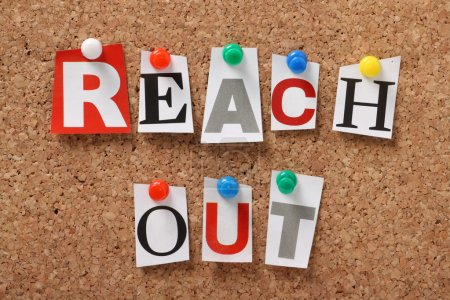 Photo for The phrase Reach Out in cut out magazine letters pinned to a cork notice board. We reach out to colleagues at work for assistance and to organizations and communities for help and support. - Royalty Free Image