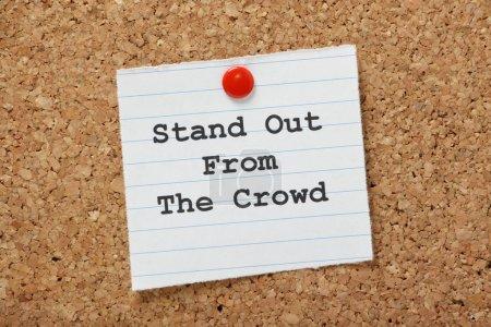 Photo pour Le membre de phrase se démarquer de la foule sur une note de papier épinglée à un panneau d'affichage Liège. Il est important de démontrer les différences ou les compétences uniques, que nous pouvons apporter à un nouvel emploi ou de la relation. - image libre de droit