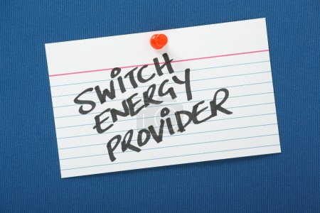 Photo for A reminder to Switch Energy Provider written on a note card pinned to a blue notice board. As power and energy providers increase their prices it pays customers to shop around for lower tariffs. - Royalty Free Image