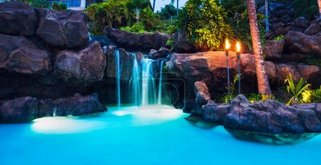 Tropical Resort Pool and Waterfall at Sunset in Ha...