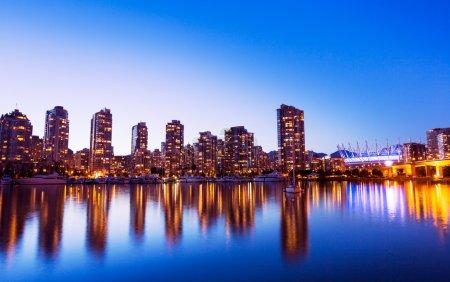 Photo pour Toits de la ville urbaine moderne reflétant dans l'eau au coucher du soleil, vancouver - image libre de droit