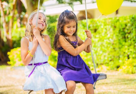 Photo for Happy little Girls Playing on Swing - Royalty Free Image