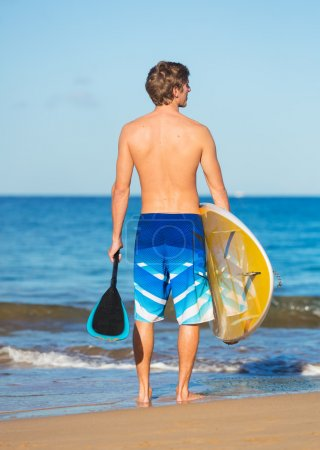 Photo for Man with Stand Up Paddle Board, SUP, on the beach in Hawaii - Royalty Free Image
