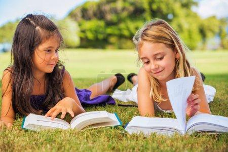 Photo pour Petites filles mignonnes lisant des livres à l'extérieur, concept d'amitié et d'apprentissage - image libre de droit