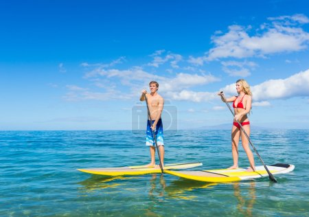 Couple Stand Up Paddle Surfing In Hawaii