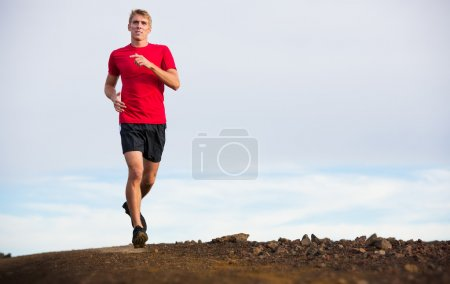 Athletic man jogging outside, training outdoors. R...