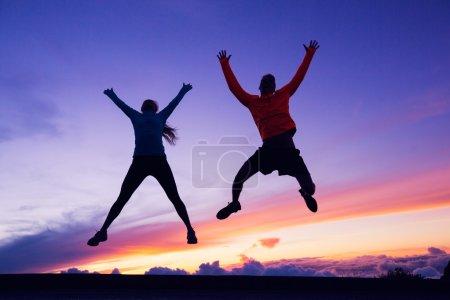 Happy man and woman having fun jumping into air at sunset