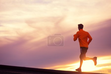 Photo for Male runner silhouette, Man running into sunset, colorful sunset sky - Royalty Free Image