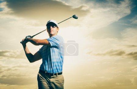 Photo pour Golfeur au coucher du soleil, club de golf balançant homme avec le ciel spectaculaire de coucher du soleil - image libre de droit