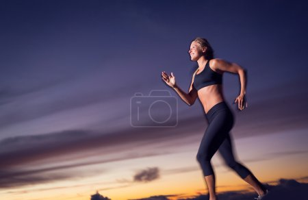 Photo for Athletic woman running jogging outside, training outdoors. Running at sunset dusk with motion blur - Royalty Free Image