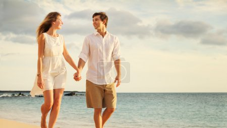 Young couple in love walking on the beach at sunset