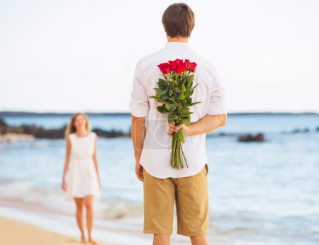 Photo for Young Couple in Love, Man holding surprise bouquet of roses for beautiful young woman, Romantic Date - Royalty Free Image