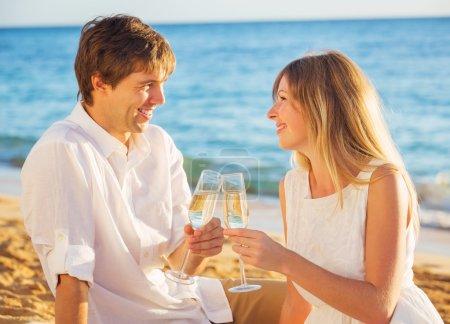 Photo pour Homme et femme amoureuse, couple profitant de champagne sur la plage tropicale au coucher du soleil, concept de lune de miel - image libre de droit