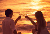 Silhouette of couple enjoying glass of champagne on tropical bea