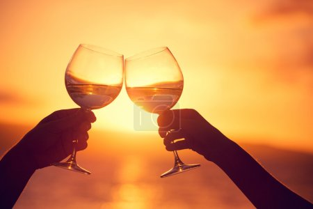 Man and woman clanging wine glasses with champagne at sunset dra