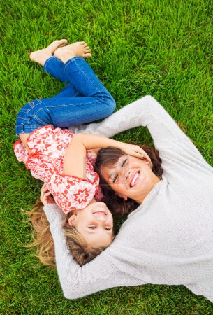 Happy mother and daughter relaxing outside on green grass. Spend