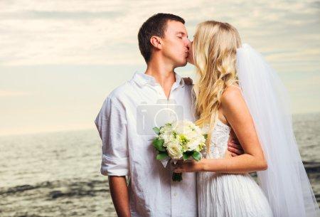 Photo pour Mariée et fiancée, Couple nouvellement marié romantique embrassant à la plage, Juste marié - image libre de droit