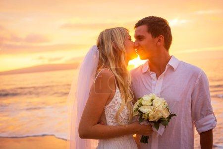 Photo pour Couple marié s'embrassant sur la plage tropicale au coucher du soleil, Hawaï Beach Wedding - image libre de droit