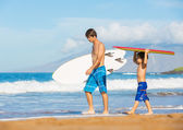 Otec a syn spolu surfování na tropické pláži v hawai