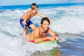 Otec a syn surfování tandemový společně chytání vln oceánu, péče