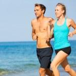 Couple running. Sport runners jogging on beach wor...