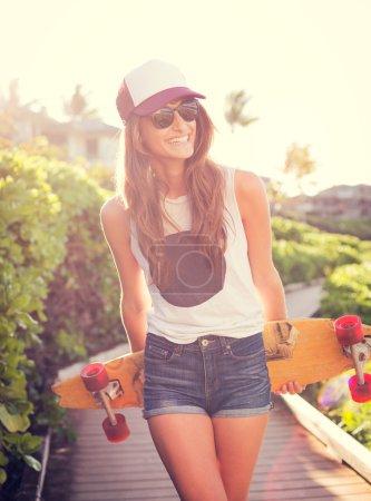 Photo pour Mode de vie, Belle jeune femme avec skateboard, rétro-éclairé au coucher du soleil - image libre de droit