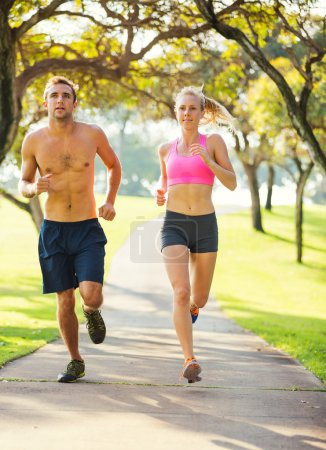 Photo for Athletic couple running together. Sport runners jogging on park trail in the early morning. Healthy lifestyle fitness concept - Royalty Free Image
