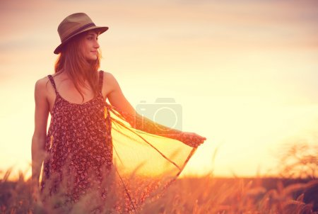 Beautiful happy woman in golden field at sunset, C...