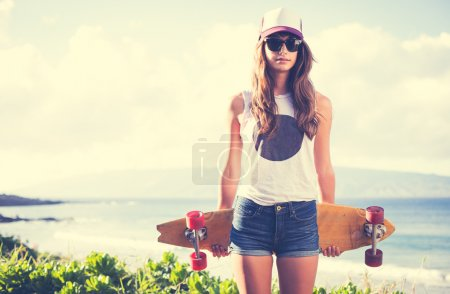 Photo pour Fille belle hipster avec board skate lunettes de soleil - image libre de droit