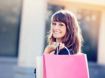 Photo pour Femme heureuse tenant des sacs à provisions et souriant au centre commercial - image libre de droit
