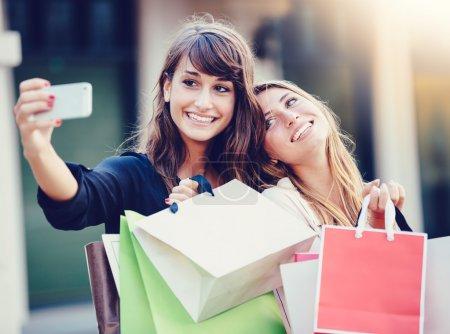 Photo pour Belles filles avec des sacs à provisions en tenant un « selfie » avec leur téléphone portable - image libre de droit