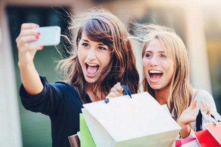 """Photo for Beautiful girls with shopping bags taking a """"selfie"""" with their cell phone - Royalty Free Image"""