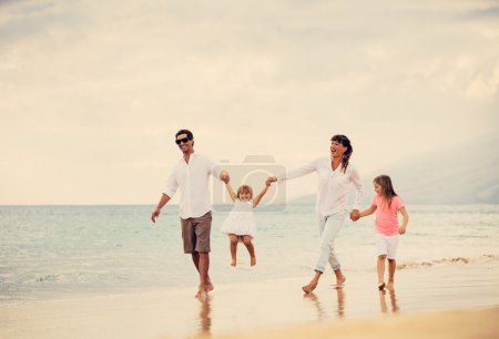 Photo for Happy Young Family have Fun Walking on Beach at Sunset - Royalty Free Image