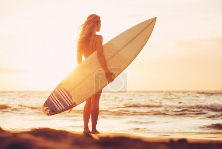 Photo for Beautiful sexy surfer girl on the beach at sunset - Royalty Free Image