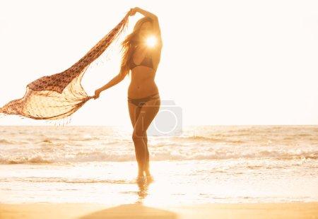 Photo pour Femme heureuse libre sur la plage au coucher du soleil. belle promenade sur la plage. mode mode de vie, rétro-éclairé, des tons ensoleillés chauds. - image libre de droit