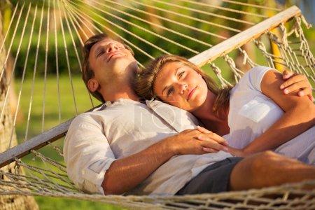 Photo pour Couple romantique relaxant dans un hamac tropical au coucher du soleil - image libre de droit