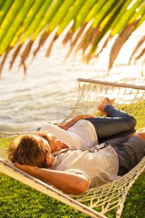 Photo for Romantic couple relaxing in tropical hammock at sunset - Royalty Free Image