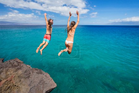 Photo for Summer fun, Friends cliff jumping into the ocean. - Royalty Free Image